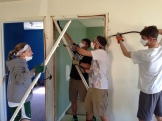 Ella, Max, John, and Ben work together to frame a door.