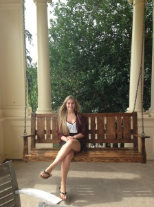 teenage girl sitting on hanging bench. two columns and a tree are in the background