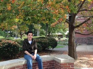 teenage boy sitting on brick structure with trees and bushes in the background.