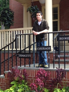 "teenage boy standing on steps with plants growing in front. ""tenacity,"" ""courage,"" and ""honor"" are written on plaques hanging from rails"